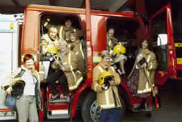 Calendar girls posing in fire engine